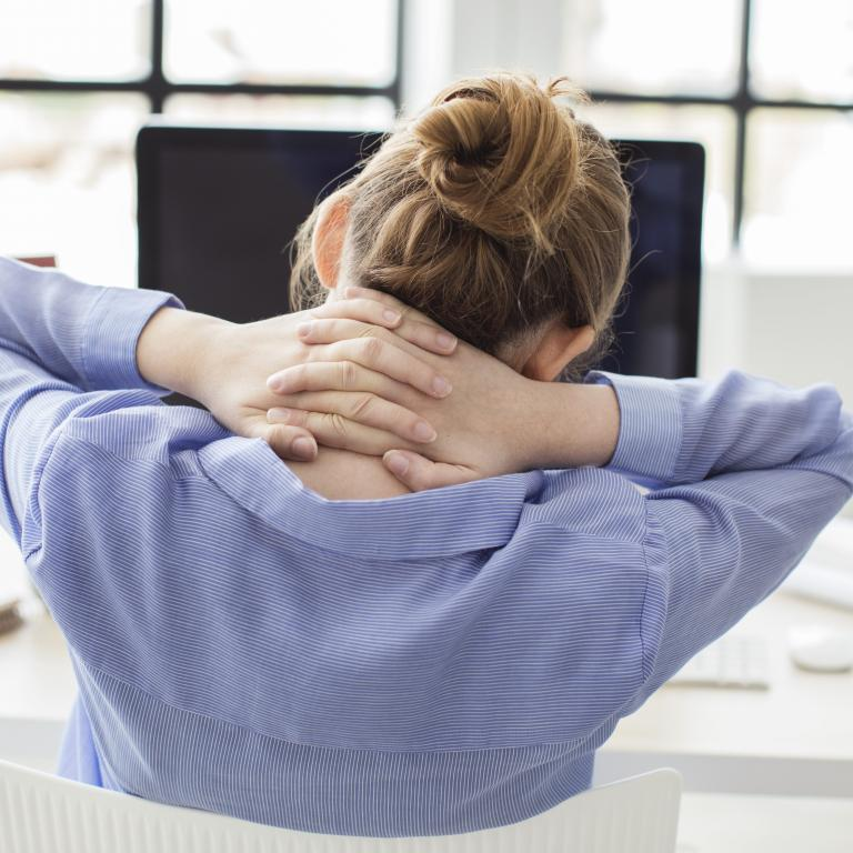 woman at desk stretching her back
