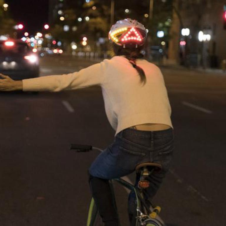 Woman on bike wearing Lumos smart bike helmet