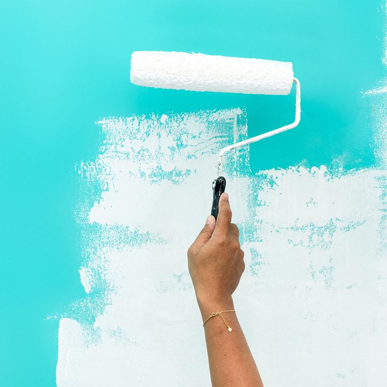 Woman's hand painting over blue wall with white paint