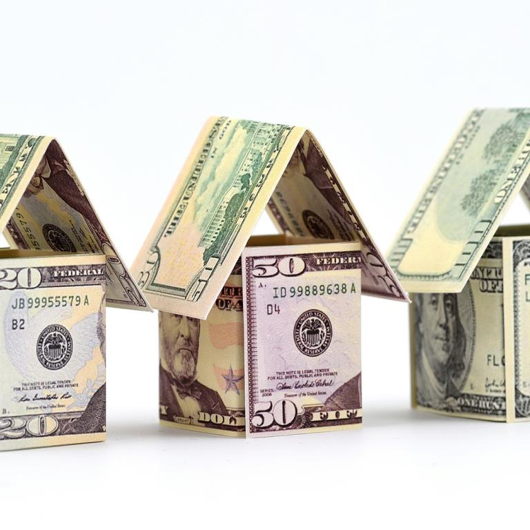 houses made out of $20, $50 and $100 bills