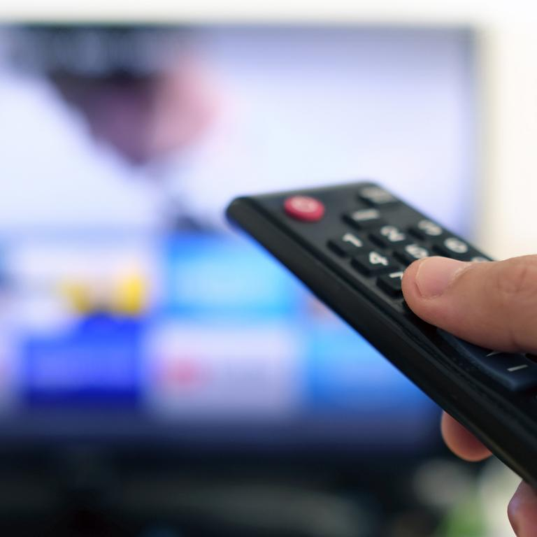hand pointing remote at TV to choose what to watch