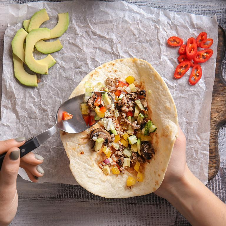 person's hands filling a tortilla to make a burrito at home
