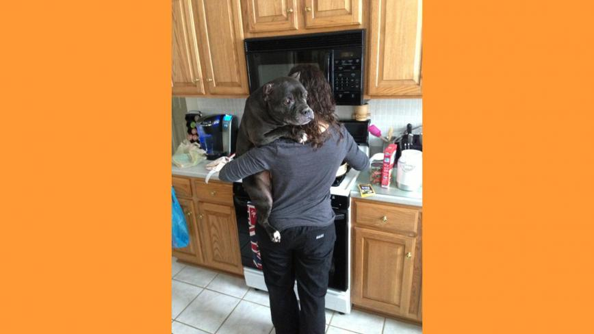Mariesa holding dog in kitchen