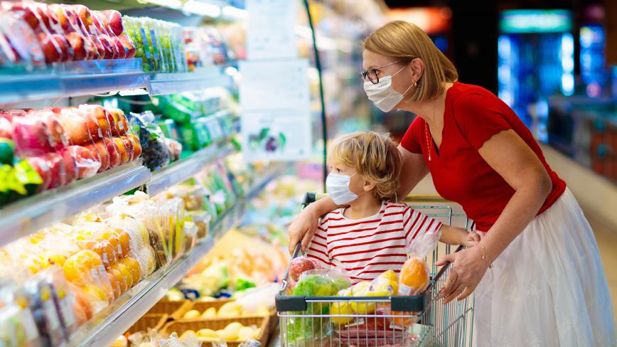 mother and child grocery shopping while wearing masks